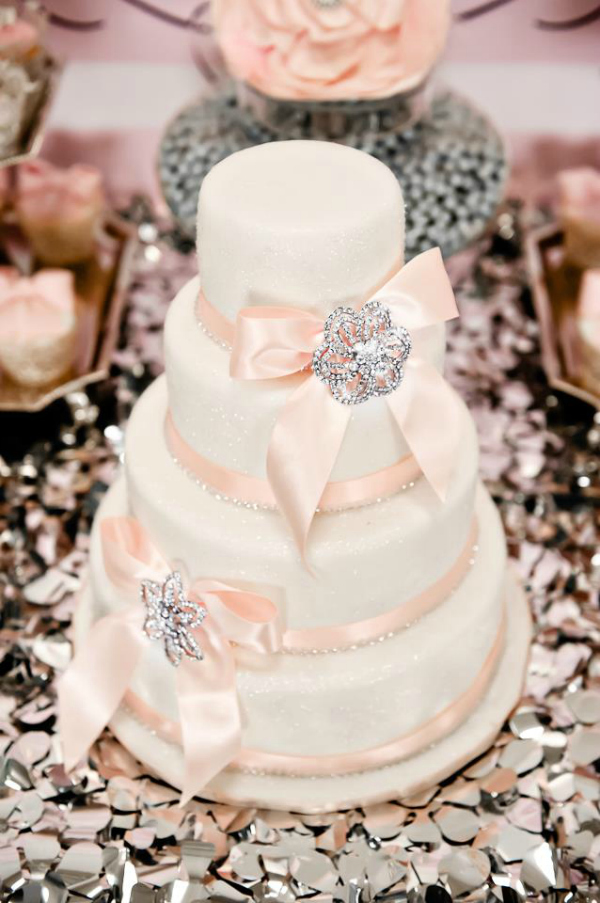 Pink and white wedding cake with ribbon and crystals