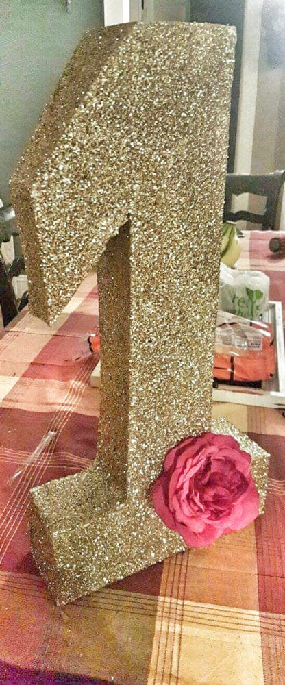 A DIY gold glitter number one decoration for a pink and gold first birthday party