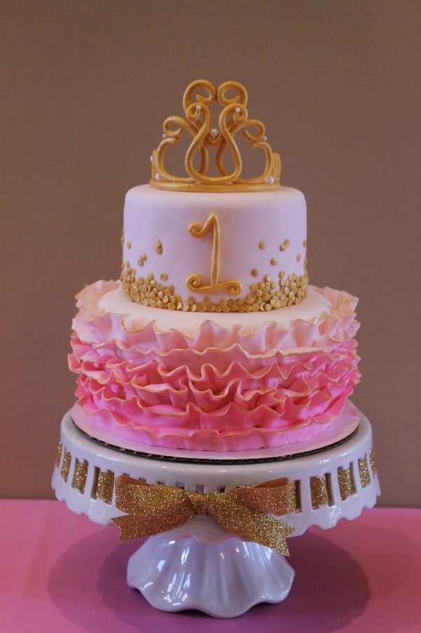 a pink and gold birthday cake with a crown topper
